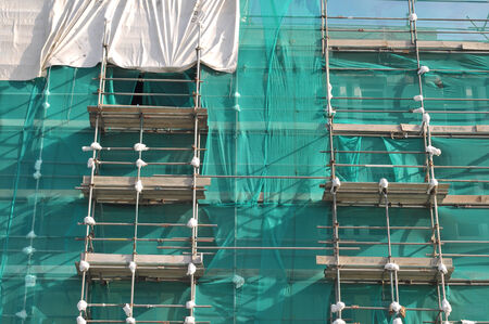 Tall building covered in scaffolding and green protection nets