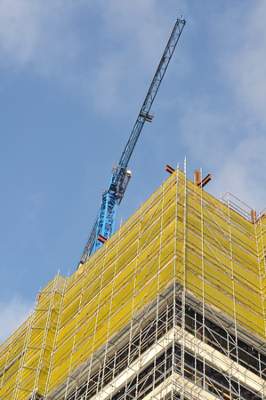 Tall building covered in scaffolding with a crane behind it