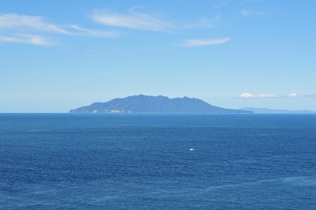 green hilly island and white fishing boat surrounded by blue sea 版權商用圖片