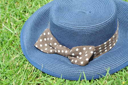 Blue hat woven from straw with white-dotted ribbon laying on grass Stock Photo