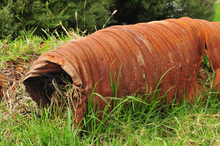 reminding: Industrial waste – rusty iron big bore pipe in the fresh green grass reminding of the recent human presence. Stock Photo