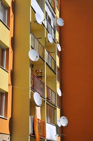 Concrete apartment building with balconies and satellite dishes.