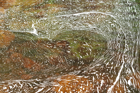 rock bottom: Thin layer of foam forming curvy patterns on the river surface. Stock Photo