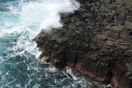 waves crashing: Waves crashing on volcanic cliffs.