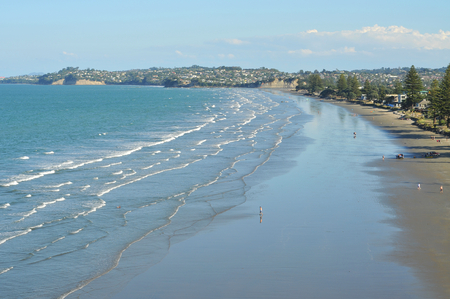 Surf waves on sandy southern Pacific beach in Orewa town in New Zealand