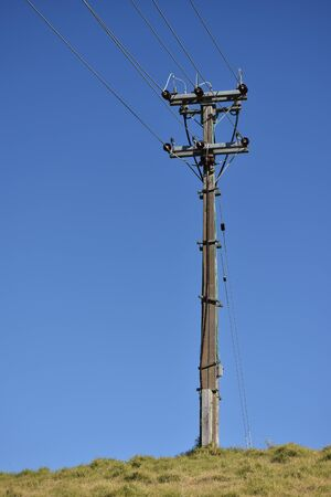 isolator: A lone electric pole on a hill.