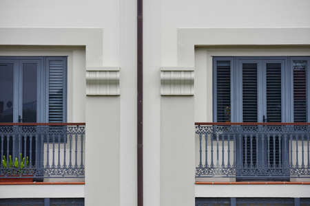 reminding: Balconies of apartments with doors and window blinds reminding mediterranean vintage style. Stock Photo