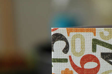 Folded piece of textured white paper with printed colourful digits on it.