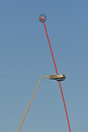 Street lamp and wind wand sculpture forming lambda shape. Stock Photo