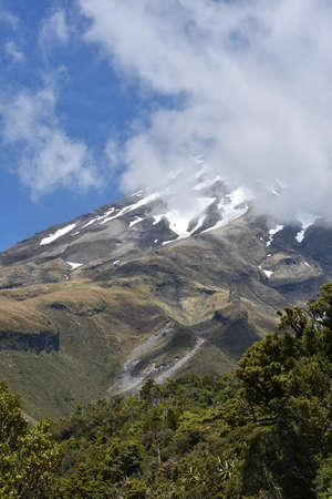 taranaki: Mt Egmont in Taranaki with patches of snow and summit hidden behind clouds. Stock Photo