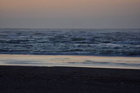 weak: Dark sandy beach with bright water reflection area in weak light at dusk.