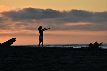 weak: Female doing exercise on sea shore in weak light at dusk. Stock Photo