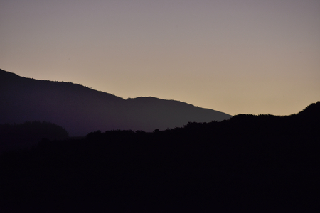 distance: Flat hills of various distance from camera in dusk light.