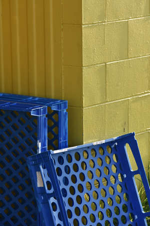 yellow block: Blue industrial food trays leaning against yellow block wall.