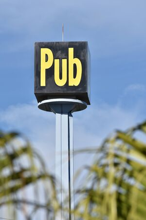visible: Cube-shaped pub sign with highly visible yellow letters on tall metal pole.