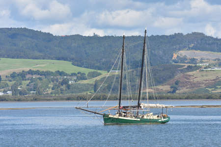 sheltered: Two masted sailship with green hull in sheltered harbour.