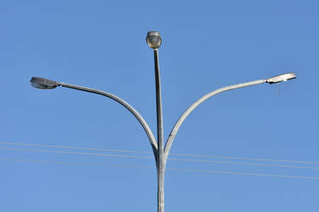 reminding: Triple street lights on metal pole and bent stems reminding of tree.