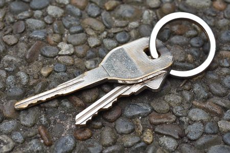 Chrome plated car keys and keyring on pavement.