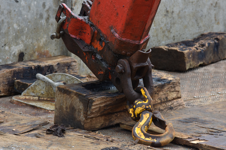 Heavy crane arm covered with oil and hook with paint peeling off on dirty barge deck. Stock Photo