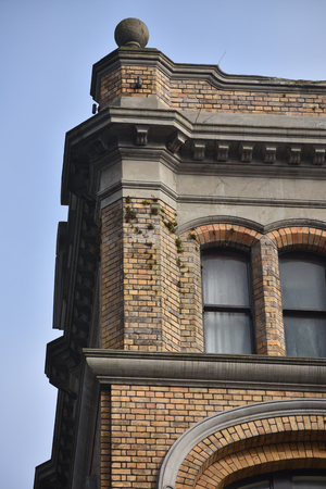 storey: Top corner of old style brick city building.