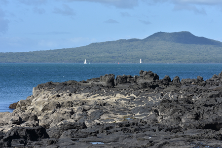 milford: View of Rangitoto volcano island from rocks in Milford. Stock Photo