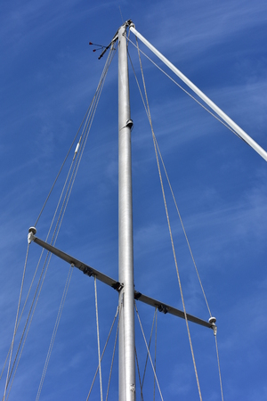cordage: Metal oval profile yacht mast with cordage. Stock Photo