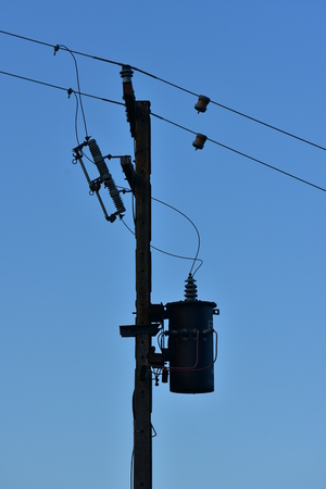 Silhouette of pole with electric wires and isolators. Stock Photo