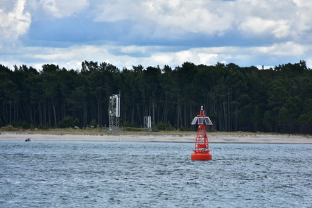 Red buoy with solar panels in shipping channel of harbour.