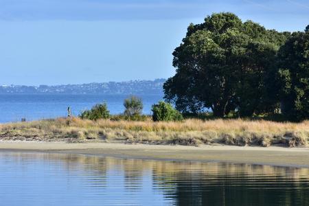 Mirror like sea around sandy coast on very calm day.
