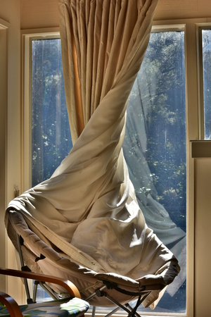 Twisted light brown curtain covering folding armchair set right next to window.