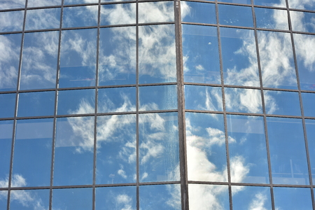 Glass wall with multiple panes held together by metal frame reflecting blue sky with white clouds.