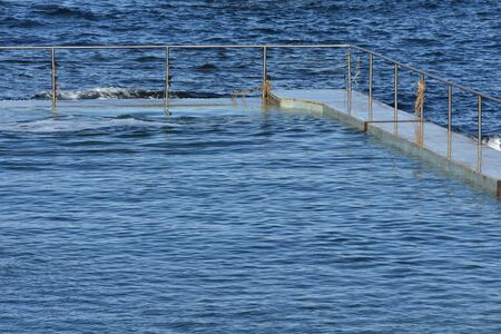 Open air ocean pool with stainless steel railing at high tide. Stock Photo
