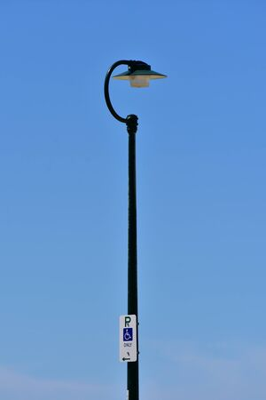 Street light on metal dark painted post with parking for disabled sign at the bottom.