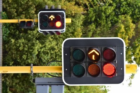 streight: Traffic lights on yellow metal poles operating during daytime. Stock Photo