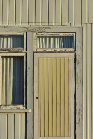 Door and window detail of weathered house with wooden cladding on outer walls. Stock Photo