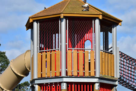 Colorful outdoor playground house with tunnel slide and rope bridge.