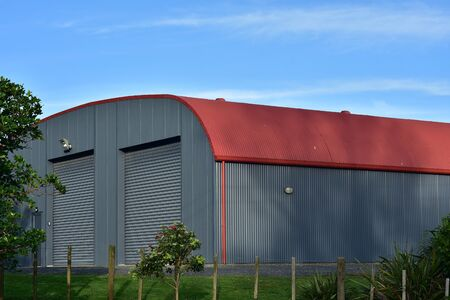 Large barn made from corrugated sheet metal painted gray on walls and red on roof.