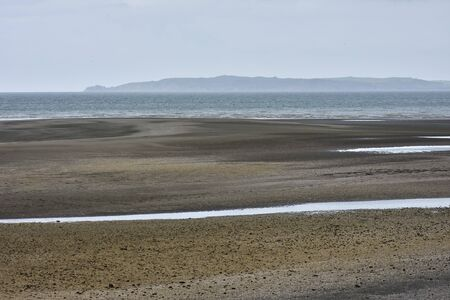 Flat beach with dark sand during low tide on overcast day.