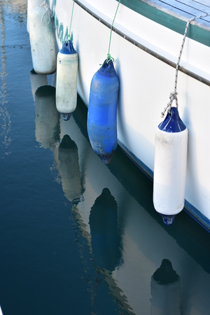 White and blue plastic fenders hanging on ropes along white ship hull.