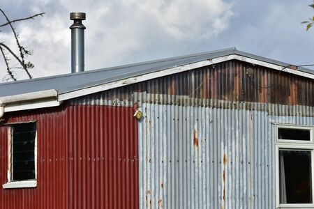 Shed made from partially rusty corrugated sheet metal panels.