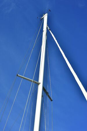 White metal sailing ship mast with ropes on blue sky background.