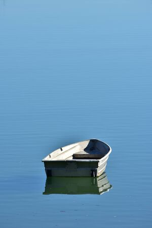 Lonely tiny tin boat reflecting on very calm blue water surface. Stock Photo