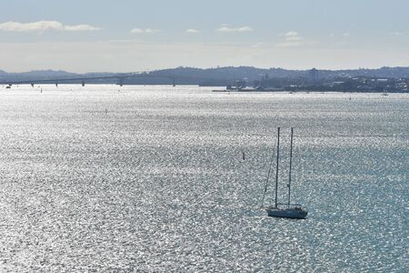 Sail ship with two masts sailing in Auckland with Devonport and Harbour Bridge in background. Stock Photo