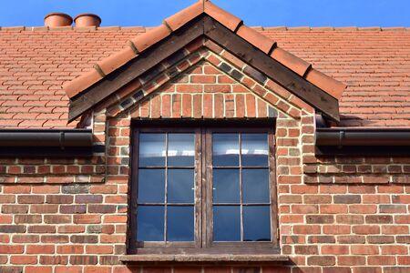 Dormer window with dark wooden frame on red brick cottage.