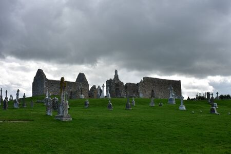 Tombstones and medieval ruins on fresh green grass in Clonmacnoise in Ireland on cloudy day.