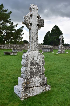 Weathered tombstone with Celtic cross on grounds of monastery of Clonmacnoise in Ireland. Stock Photo