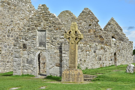 Ruins of medieval stone Christian church called Temple Dowling with Celtic sandstone high cross in Clonmacnoise in Ireland.