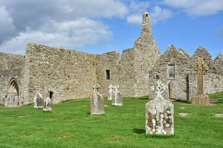 Ruins of medieval stone Christian cathedral called Temple MacDermot with other church ruins and Celtic high cross in Clonmacnoise in Ireland. Stock Photo