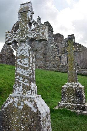 Croci celtiche e rovine di chiese medievali in pietra nel monastero di Clonmacnoise in Irlanda. Archivio Fotografico - 96963628