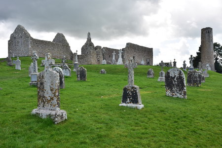 Weathered tombstones with ruins of medieval churches and round tower in background in monastery of Clonmacnoise in Ireland.